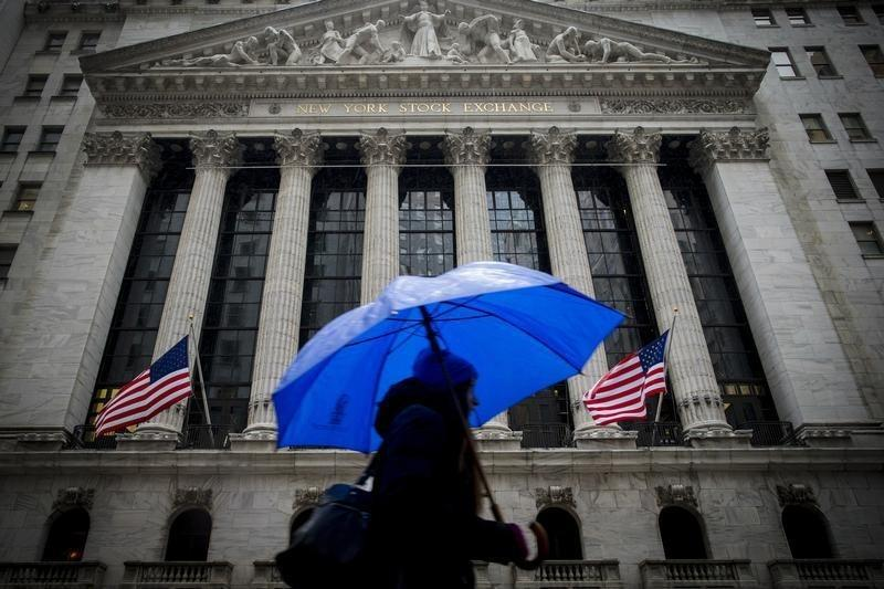 A morning commuter carries an umbrella as she passes by the NYSE during a winter storm in New York
