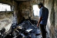 An Israeli man stands in his fire-damaged home, burnt during recent violence between Arab and Jewish Israelis in Lod