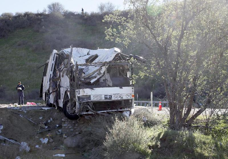 FILE - In this Feb. 4, 2013 file photo, an official takes notes  at the scene of a tour bus crash near San Bernardino, Calif. Teams of federal inspectors will target bus companies with a history of problems as part of a national crackdown aimed at weeding out unsafe operators in response to recent deadly tour bus accidents, the government said Thursday.  ( AP Photo/Nick Ut, File)