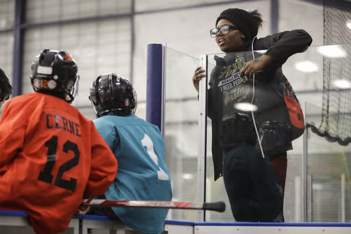 In this Feb. 21, 2019 photo Wylla Johnson, right, talks to her brother Malakye, center left, before he takes part in Snider Hockey practice at the Scanlon Ice Rink in Philadelphia. (AP Photo/Matt Rourke)