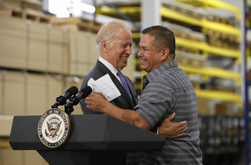 Vice President Joe Biden embraces Bobrick employee Rigoberto Hernandez, who has worked for the company for 29 years. The vice president visited the Bobrick factory to promote a higher minimum wage.