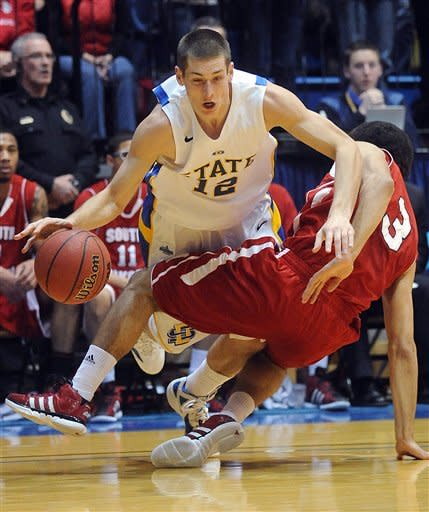 South Dakota State's Brayden Carlson (12) trips over South Dakota's Steve Tecker (3) during an NCAA college basketball game, Thursday, Jan. 12, 2012, in Brookings, S.D. South Dakota State won 86-56. (AP Photo/The Argus Leader, Elisha Page) THE DAILY REPUBLIC OUT; NO SALES