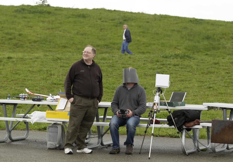 In this March, 28, 2012, photo, Andreas Oesterer, right, uses a video link to fly a drone at a waterfront park as Mark Harrison, left, watches in Berkeley, Calif. Interest in the domestic use of drones is surging among public agencies and private citizens alike, including a thriving subculture of amateur hobbyists, even as the prospect of countless tiny but powerful eyes circling in the skies raises serious privacy concerns. (AP Photo/Eric Risberg)