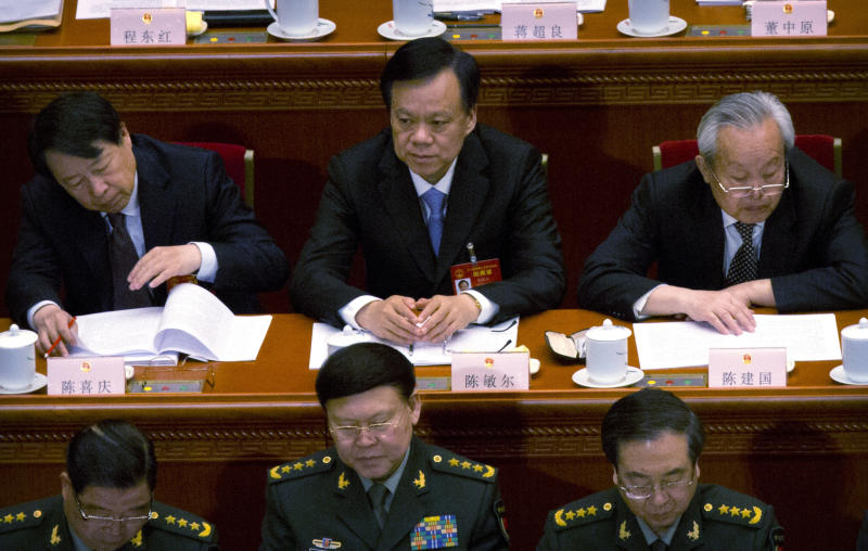 In this March 5, 2017 photo, Chen Min-er, center, the then-party secretary of Guizhou, attends the opening session of China's National People's Congress (NPC) at the Great Hall of the People in Beijing. A Chinese politician considered a potential future leader has been replaced as head of the central mega-city of Chongqing amid reports he is facing a graft investigation. The Chongqing government said on its website Saturday, July 15, 2017, that Sun Zhengcai was being replaced as head of the city's Communist Party committee by Chen Min-er. (AP Photo/Mark Schiefelbein)