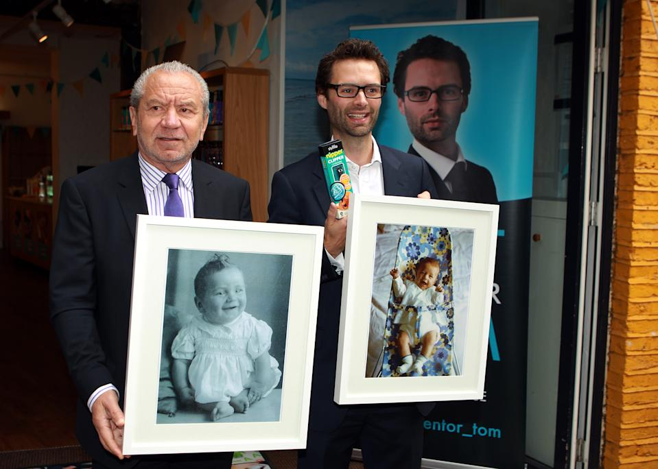Lord Sugar and inventor Tom Pellereau, who won the 2012 series of The Apprentice, hold pictures of themselves as babies in Convent Garden, London, during the unveiling of their latest product, a nail clipper for children.
