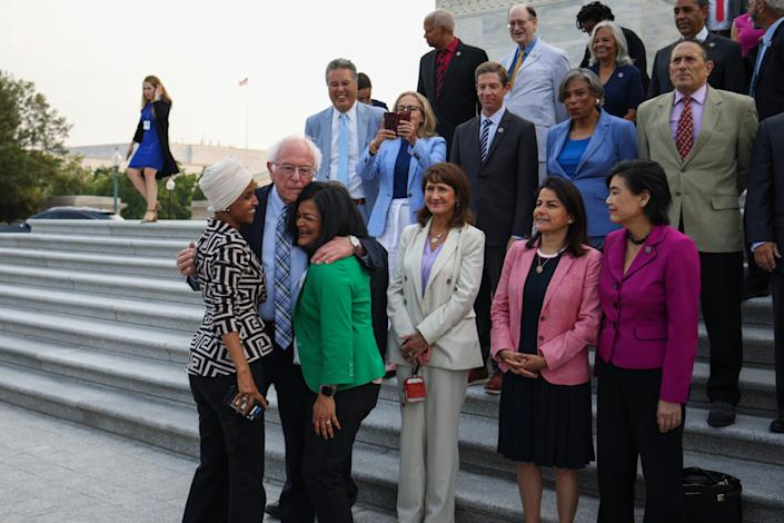 Sen. Bernie Sanders, I-Vt., center, greets Rep. Ilhan Omar D-Minn., left, and Rep. Pramila Jayapal, D-Wash., before a group photo with members of the Congressional Progressive Caucus in front of the U.S. Capitol Building on July 19, 2021, in Washington, D.C.