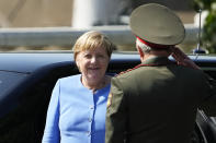 German Chancellor Angela Merkel, left, arrives for a wreath laying ceremony at the Tomb of Unknown Soldier in Moscow, Russia, Friday, Aug. 20, 2021, prior to talks with Russian President Vladimir Putin. The talks between Merkel and Putin are expected to focus on Afghanistan, the Ukrainian crisis and the situation in Belarus among other issues. (AP Photo/Alexander Zemlianichenko, Pool)