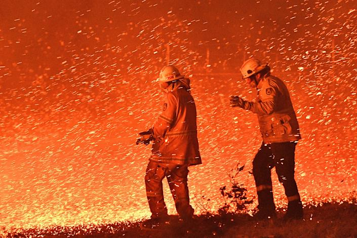 Firefighters struggle against strong winds in an effort to secure nearby houses from bushfires near the town of Nowra in the Australian state of New South Wales, December 31, 2019.