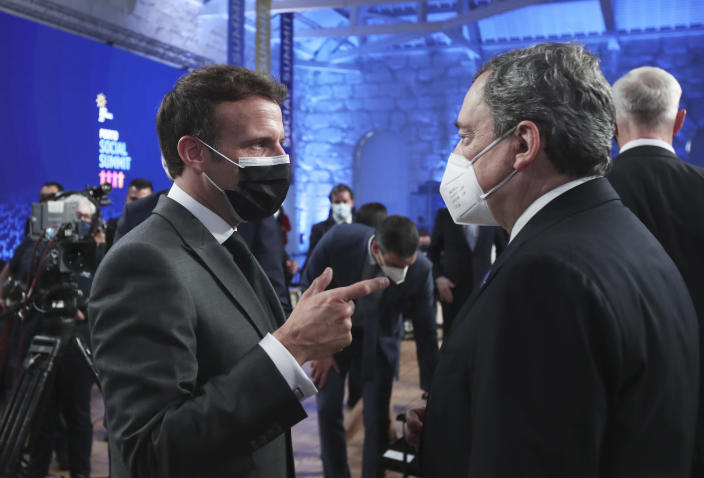 French President Emmanuel Macron, left, speaks with Italy's Prime Minister Mario Draghi during the opening ceremony of an EU summit at the Alfandega do Porto Congress Center in Porto, Portugal, Friday, May 7, 2021. European Union leaders are meeting for a summit in Portugal on Friday, sending a signal they see the threat from COVID-19 on their continent as waning amid a quickening vaccine rollout. Their talks hope to repair some of the damage the coronavirus has caused in the bloc, in such areas as welfare and employment. (AP Photo/Luis Vieira, Pool)