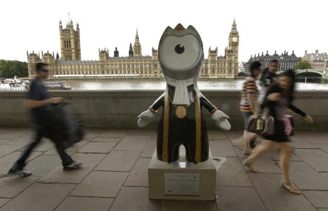 People walk by an Olympic mascot, painted in the likeness of a member of Parliament, across the River Thames from Parliament on Saturday, July 21, 2012, in London. The statue is one of 84 fiberglass sculptures of the mascots Wenlock or Mandeville that were painted by various artists and erected across the city for the 2012 London Olympic Games. (AP Photo/Charlie Riedel)
