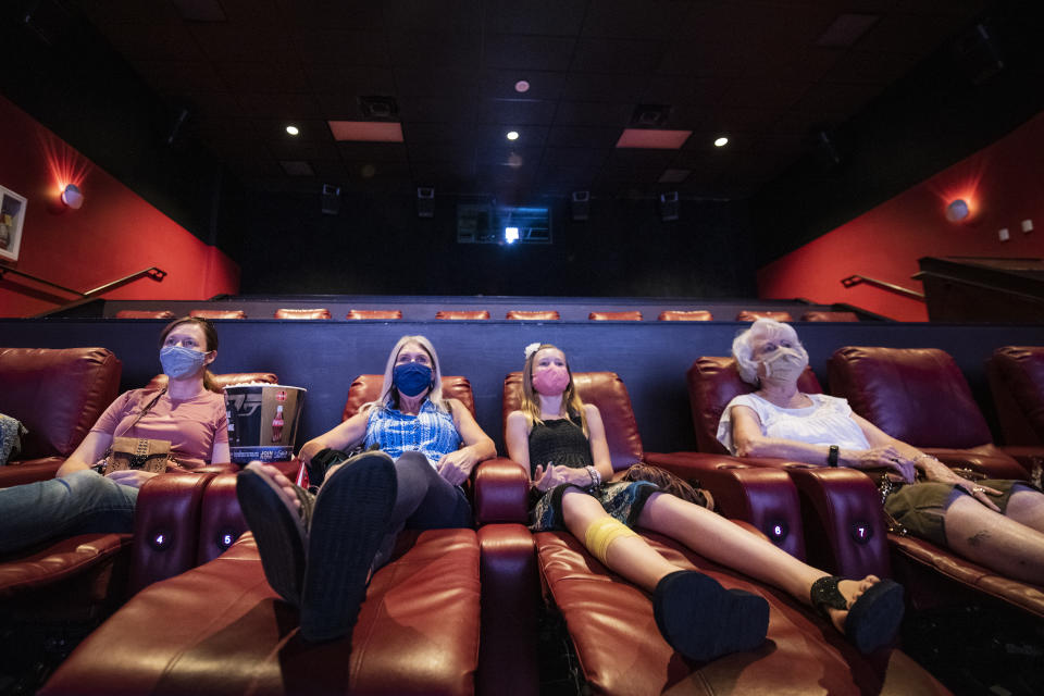 """DENVER, COLORADO - AUGUST 20: Movie goers watch a film at the AMC Highlands Ranch 24 on August 20, 2020 in Highlands Ranch, Colorado. AMC Theatres reopened more than 100 of its movie theaters across the United States today, with new safety precautions in place, for the first time since closing in March because of the coronavirus (COVID-19) pandemic. In celebration of its 100th anniversary, the world's largest theater chain is welcoming guests back with a """"Movies in 2020 at 1920 Prices"""" promotion for one day by offering 15-cent tickets to classic and previously-released films and $5 concession items. Starting on August 21, older movies will be shown for $5 a ticket. According to AMC, enhanced cleaning and safety protocols include disinfecting theaters before each show, mandatory face coverings for employees and customers, upgraded air filtration systems where possible, and high-touch points cleaned throughout the day. Hand sanitizer and disinfectant wipes are available throughout the theaters, auditoriums are at 40 percent capacity or less, and concession menus have been simplified for shorter lines and quicker service.  (Photo by Tom Cooper/Getty Images)"""