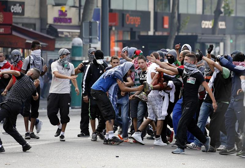 Demonstrators carry an injured man as others clash with French riot police on the Republique square in Paris on July 26, 2014 (AFP Photo/Francois Guillot)