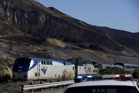 Passengers take pictures from an northbound Amtrak train in the aftermath of a wildfire in the Solimar Beach area of Ventura County, California