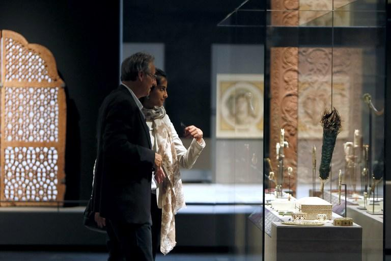 "Visitors examine Islamic art works on September 17, 2012 in Paris, during a press visit of the new Department of Islamic Arts at the Louvre, the largest of its kind in Europe, with 3,000 artefacts on display, gathered from Spain to India and dating back to the seventh century AD. Intended to celebrate ""The Radiant Face of a Great Civilization"" the 100-million-euro project - largely financed by donors from across the Islamic world - will be inaugurated by French President ahead of its official opening on September 18. AFP PHOTO / KENZO TRIBOUILLARD"