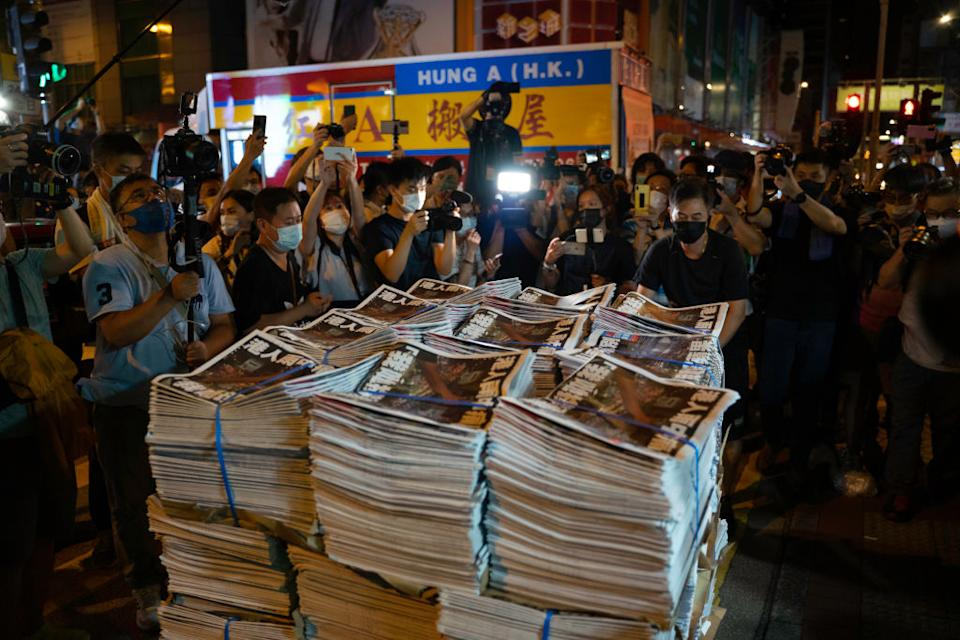 Stacks of the final edition of the Apple Daily surrounded by people.
