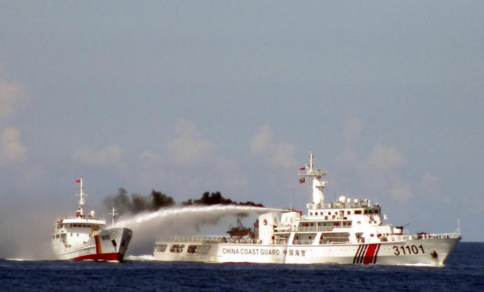 In this Sunday, May 4, 2014 image made from video released by Vietnam Coast Guard, a Chinese coast guard vessel, right, fires water cannon at a Vietnamese vessel off the coast of Vietnam. China insisted Thursday, May 8, 2014 it had every right to drill for oil off Vietnam's coast and warned its neighbor to leave the area around the deep-sea rig where Chinese and Vietnamese ships are engaged in a tense standoff. With the ships jostling each other since China deployed the rig last weekend in disputed South China Sea waters, the United States warned both sides to de-escalate tensions and urged China to clarify its claims to the territory. (AP Photo/Vietnam Coast Guard)