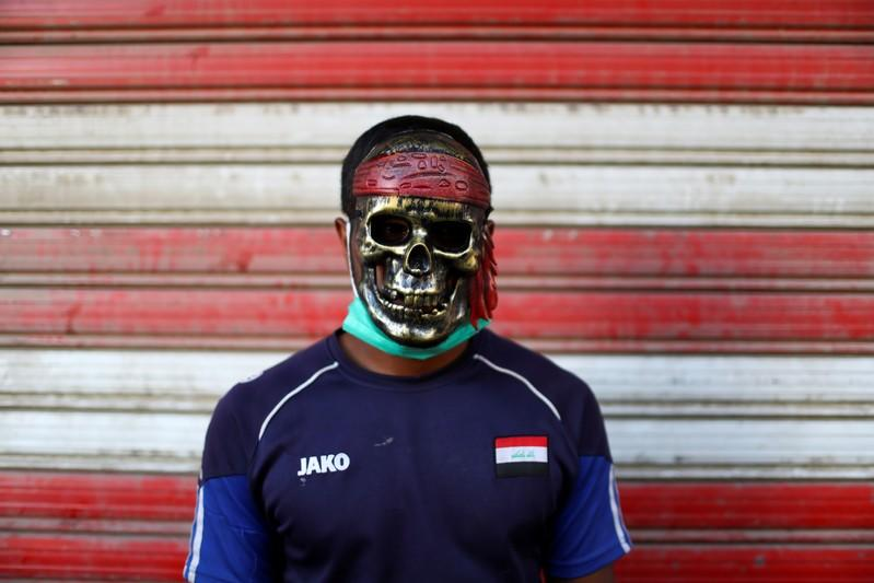 An Iraqi demonstrator wears a mask during the ongoing anti-government protests in Baghdad