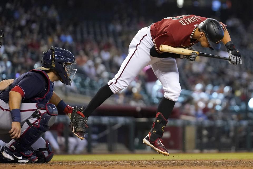 Arizona Diamondbacks' Nick Ahmed, right, jumps out of the way of an inside pitch as Washington Nationals catcher Alex Avila, left, makes the catch during the seventh inning of a baseball game Sunday, May 16, 2021, in Phoenix. (AP Photo/Ross D. Franklin)