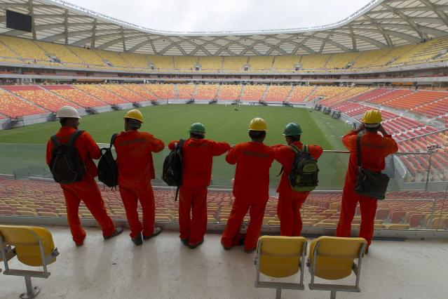 Workers look out over the Arena Amazonia soccer stadium three days before its scheduled inauguration, in Manaus March 6, 2014. The Arena Amazonia will host four matches of the 2014 World Cup. REUTERS/Bruno Kelly (BRAZIL - Tags: SPORT SOCCER WORLD CUP)