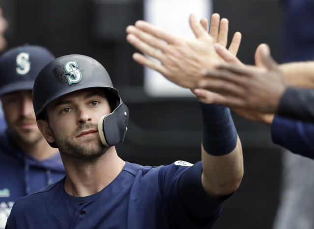 Seattle Mariners' Mitch Haniger celebrates with teammates after scoring on a one-run single by Edwin Encarnacion during the third inning of a baseball game against the Chicago White Sox in Chicago, Sunday, April 7, 2019. (AP Photo/Nam Y. Huh)