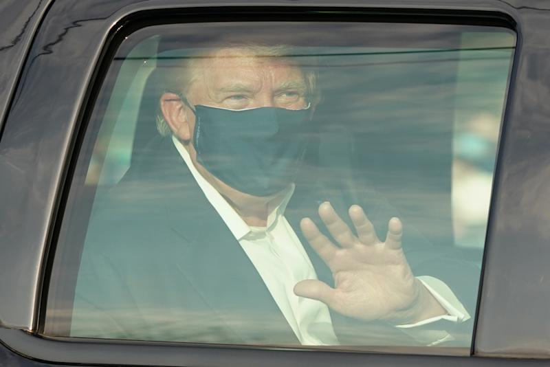 President Trump wears a face mask and waves from inside a vehicle