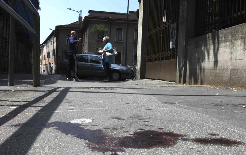 People talk as a pool of blood stains the road where an immigrant from Ghana went on a rampage with a pickaxe in Milan at dawn Saturday, May11, 2013 killing a passerby and wounding four others in an apparently random attack, police said. The attack, which police say was the work of an illegal immigrant with a criminal record, immediately fueled a political debate raging for years over whether Italy should crack down harder on immigrants or facilitate their path toward citizenship, as recently lobbied for by Italy's first black Cabinet minister, who had immigrated from Congo. Carabinieri paramilitary police in Milan said the 21-year-old attacker was taken into custody shortly after the attacks in a residential area on the northern outskirts of the city. (AP Photo/Stefano De Grandis, Lapresse)