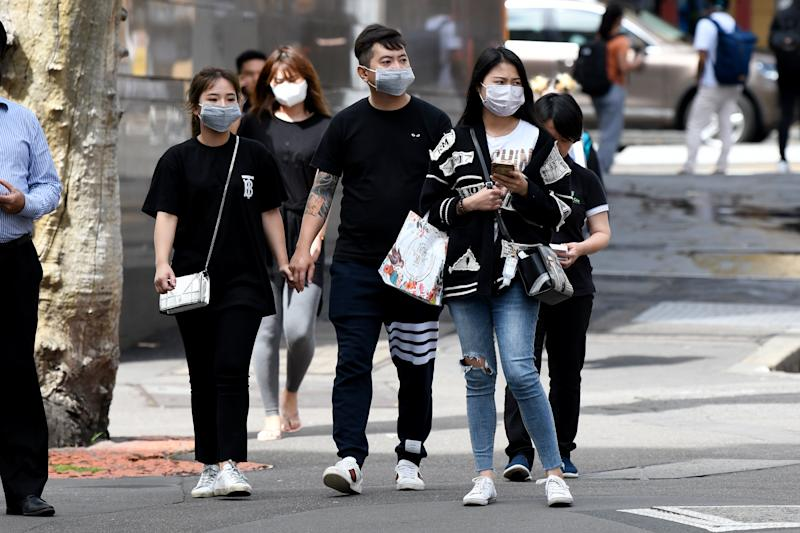 People are seen wearing face masks in Sydney on Monday amid a spike in cases across the city.