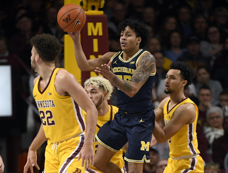 Michigan's Eli Brooks (55) passes the ball away from Minnesota's Gabe Kalscheur (22), Jarvis Omersa (21) and Payton Willis (0) in the first half during an NCAA college basketball game on Sunday, Jan. 12, 2020, in Minneapolis. (AP Photo/Hannah Foslien)