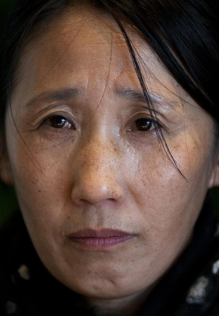 Chinese petitioner Wang Xiulan pauses while she speaks during an interview in Beijing Tuesday, Nov. 6, 2012. Wang has been trying for two decades to draw central government attention to what she says is local police mishandling of an assault she suffered in her native Harbin city. Wang narrowly avoided being forced back home by assuming a fake identity and is now in hiding, but her ordeal paints a picture of the police dragnet aimed at preventing anyone perceived as a threat or a troublemaker from being in Beijing when an all-important leadership transition begins Thursday, Nov. 8. (AP Photo/Alexander F. Yuan)