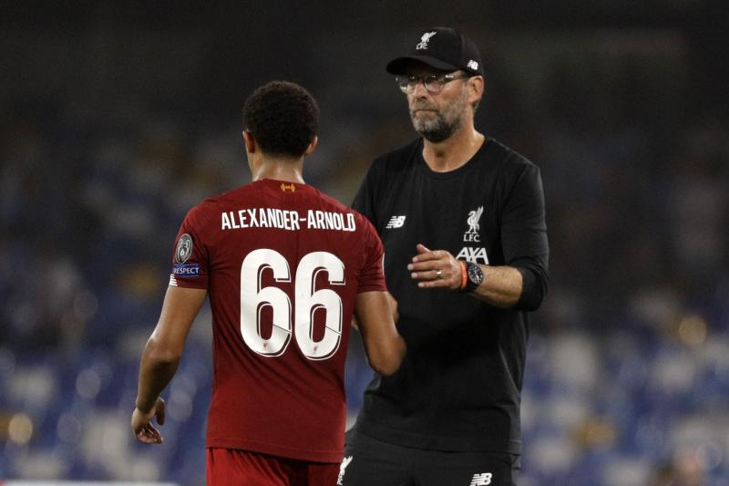 Liverpool's manager Jurgen Klopp, right, shake shards with Trent Alexander-Arnold reacts after the Champions League Group E soccer match between Napoli and Liverpool, at the San Paolo stadium in Naples, Italy, Tuesday, Sept. 17, 2019. Napoli won 2-0. (AP Photo/Gregorio Borgia)