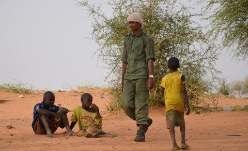A group of Mali army deserters walks past children in a camp near Niamey on May 25. Mali's embattled transitional government has rejected a rebel alliance's declaration of an Islamic state in the vast desert north, a move that has plunged the nation closer to breakup two months after a coup