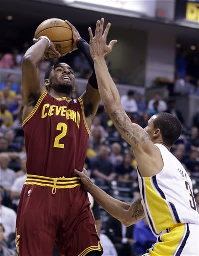 Cleveland Cavaliers guard Kyrie Irving, left, shoots over Indiana Pacers guard George Hill in the first half of an NBA basketball game in Indianapolis, Tuesday, April 9, 2013. (AP Photo/Michael Conroy)
