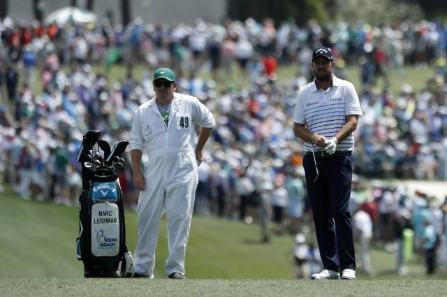 Marc Leishman of Australia and his caddie Matthew Kelly look over their second shot on the first fairway during second round play of the 2018 Masters golf tournament at the Augusta National Golf Club in Augusta, Georgia, U.S., April 6, 2018. REUTERS/Jonathan Ernst