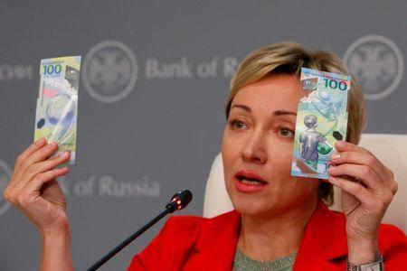 FILE PHOTO: Russian central bank deputy chairwoman Olga Skorobogatova holds the newly designed 100-rouble banknotes dedicated to the 2018 FIFA World Cup, during a news conference in Moscow, Russia May 22, 2018. REUTERS/Sergei Karpukhin/File Photo