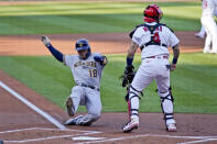 Milwaukee Brewers' Keston Hiura (18) scores past St. Louis Cardinals catcher Yadier Molina during the second inning in the first game of a baseball doubleheader Friday, Sept. 25, 2020, in St. Louis. (AP Photo/Jeff Roberson)