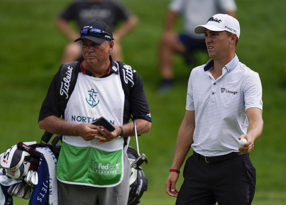 Justin Thomas, right, speaks with his caddie after making his putt on the eighth green in the first round of play at the Northern Trust golf tournament, Thursday, Aug. 19, 2021, at Liberty National Golf Course in Jersey City, N.J. (AP Photo/John Minchillo)