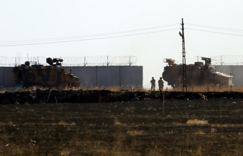 In this photo taken from the outskirts of the village of Alakamis, in Idil province, southeastern Turkey, Turkish army vehicles return to Turkey from Syria after conducting a joint patrol with Russian forces, Friday, Nov. 8, 2019. The Britain-based Syrian Observatory for Human Rights says a protester has been killed when he was run over in the village of Sarmasakh, Syria near the border by a Turkish vehicle during a joint patrol with Russia.The man was among residents who pelted with shoes and stones Turkish and Russian troops who were conducting their third joint patrol in northeastern Syria, under a cease-fire deal brokered by Moscow that forced Kurdish fighters to withdraw from areas bordering Turkey. (AP Photo/Mehmet Guzel)