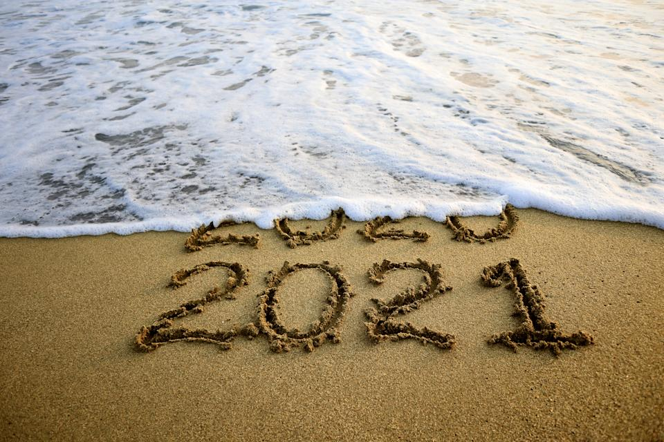 New year 2021 and old year 2020 on sandy beach with waves