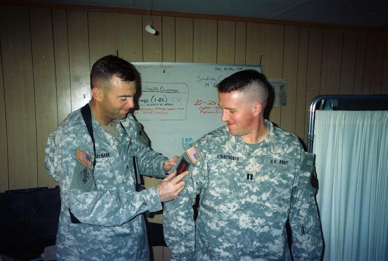 """In this Autumn 2006 photo provided by Brock McNabb, McNabb places a """"combat patch"""" on Pete Linnerooth's uniform at their office in Baghdad, denoting that he had been in-country long enough to earn the badge of honor and is officially a combat veteran. Capt. Linnerooth was an Army psychologist who counseled soldiers during some of the fiercest fighting in Iraq. Hundreds upon hundreds sought his help. For nightmares and insomnia. For shock and grief. And for reaching that point where they just wanted to end it all. Linnerooth did such a good job his Army comrades dubbed him The Wizard. His """"magic"""" was deceptively simple: an instant rapport with soldiers, an empathetic manner, a big heart. (AP Photo/Brock McNabb)"""