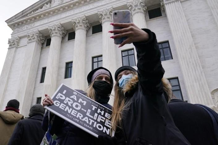 Andrea Albury, left, and her daughter Ella Albury, 15, both from Lynchburg, Va., take a selfie with the back of the Supreme Court as they participate in the 48th Annual March for Life in Washington, Friday, Jan. 29, 2021. (AP Photo/Susan Walsh)