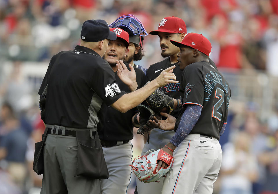 Home plate umpire Andy Fletcher, left, speaks with Miami Marlins pitcher Pablo Lopez, second from right, shortstop Miguel Rojas, second from left, and second baseman Jazz Chisholm Jr. (2) during the first inning of a baseball game against the against the Atlanta Braves on Friday, July 2, 2021, in Atlanta. Lopez and manager Don Mattingly were both ejected. (AP Photo/Ben Margot)