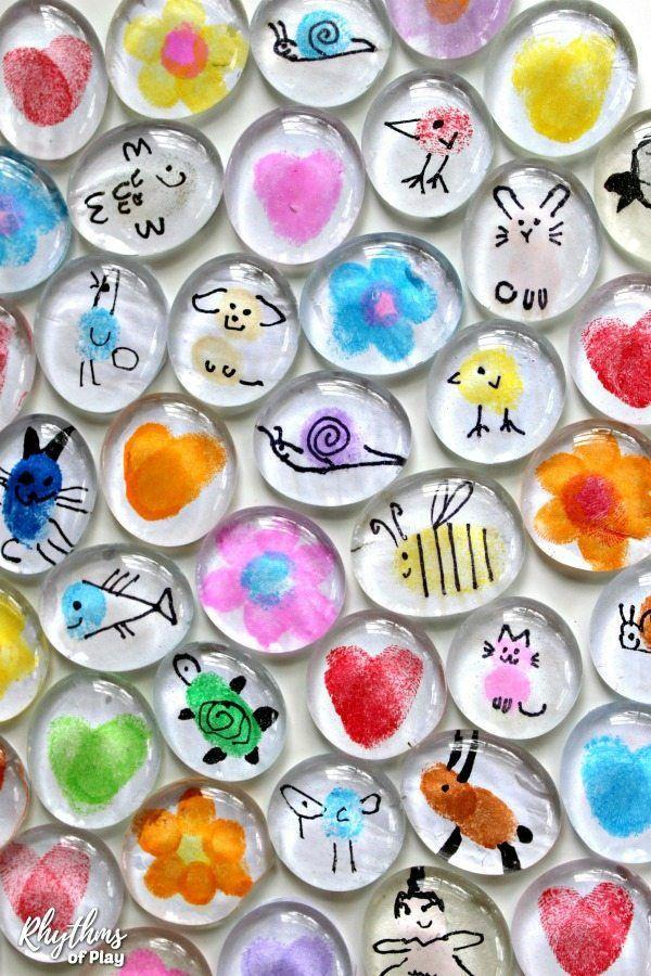 """<p>There's no shortage of thumbprint creations your kids can come up with to wow Mom—not to mention they'll look incredible hanging from the fridge.</p><p><strong>Get the tutorial at <a href=""""https://rhythmsofplay.com/fingerprint-art-glass-magnets/"""" rel=""""nofollow noopener"""" target=""""_blank"""" data-ylk=""""slk:Rhythms of Play"""" class=""""link rapid-noclick-resp"""">Rhythms of Play</a>. </strong></p><p><strong><a class=""""link rapid-noclick-resp"""" href=""""https://www.amazon.com/JUMBO-CLEAR-GLASS-MARBLE-FILLER/dp/B01JUX3MUW/?tag=syn-yahoo-20&ascsubtag=%5Bartid%7C10050.g.4233%5Bsrc%7Cyahoo-us"""" rel=""""nofollow noopener"""" target=""""_blank"""" data-ylk=""""slk:SHOP GLASS GEMS"""">SHOP GLASS GEMS</a><br></strong></p>"""