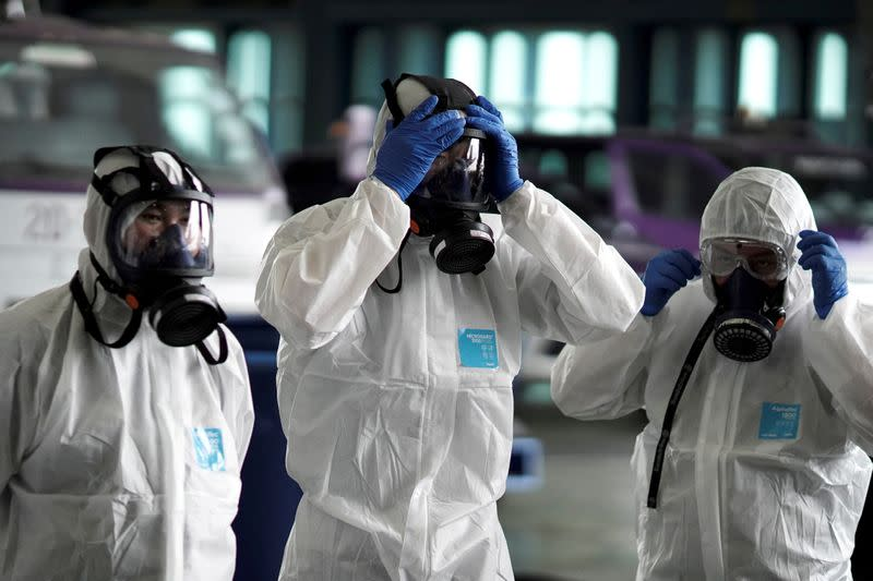 FILE PHOTO: Members of the Thai Airways crew prepare themselves before disinfecting the cabin of an aircraft of the national carrier during a procedure to prevent the spread of the coronavirus at Bangkok's Suvarnabhumi International Airport