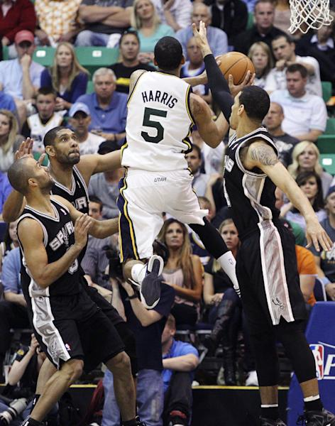Utah Jazz point guard Devin Harris (5) gets past the defense of San Antonio Spurs point guard Tony Parker (9), of France, center Tim Duncan (21) and guard Danny Green (4) to score during the first half of Game 3 in their first-round NBA basketball playoff series, Saturday, May 5, 2012, in Salt Lake City. (AP Photo/Colin E Braley)