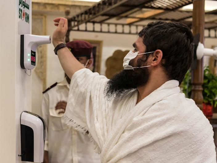 A Muslim pilgrim wearing a protective face mask has his temperature checked as he arrives in Mina, Saudi Arabia, on July 29, 2020.