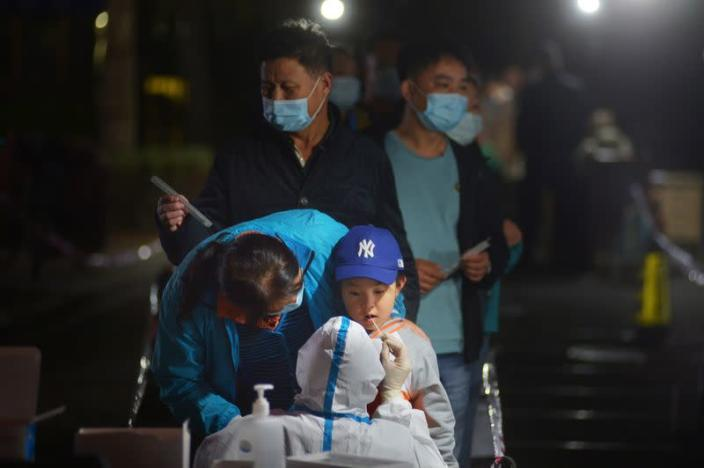 Medical worker collects a swab from a child for nucleic acid testing, in Qingdao