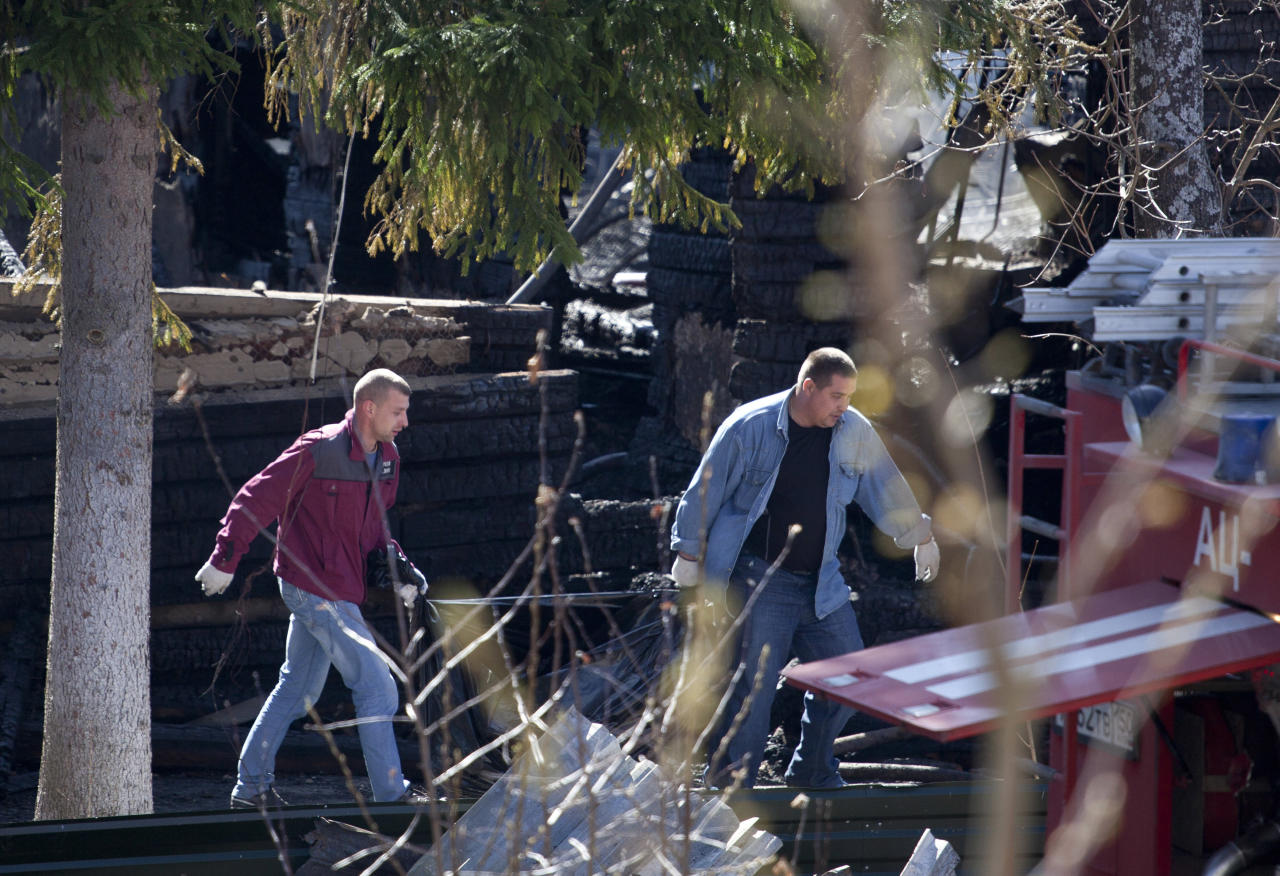 Investigators carry a body of a victim at a site of a fire of a psychiatric hospital Friday morning, April 26, 2013. At least 38 people died in a fire in a psychiatric hospital outside Moscow late Thursday night. Police said the fire, which broke out at about 2 a.m. local time (6 p.m. Eastern, 2200 GMT) in the one-story hospital in the Ramenskoye settlement, was caused by a short circuit. (AP Photo/Pavel Sergeyev)