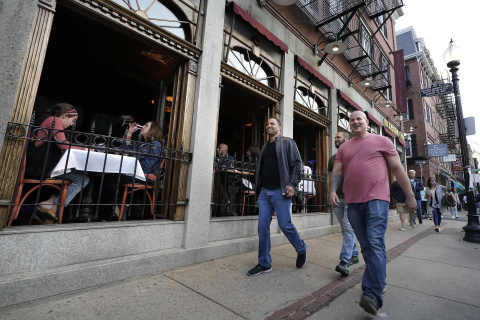 FILE - In this March 25, 2021, file photo, people, right, walk past diners seated near open windows, left, in a restaurant on a busy street in the historic North End neighborhood of Boston. In Massachusetts, where the seven-day rolling average of daily new cases has risen to over 2,100 new cases per day, the Massachusetts Public Health Association called on Republican Gov. Charlie Baker to reinstate public health measures. The group urged Baker to limit indoor dining capacity and other indoor activities, saying the rise in cases and hospitalizations followed Baker's decision to loosen those restrictions. (AP Photo/Steven Senne, File)