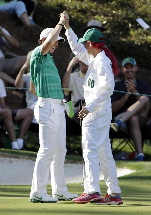 Tennis player Caroline Wozniacki high fives with her fiancee Rory McIlroy, of Northern Ireland, after Wozniacki putted on the ninth hole during the par three competition at the Masters golf tournament Wednesday, April 9, 2014, in Augusta, Ga. (AP Photo/David J. Phillip)
