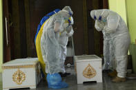 Siam Nonthaburi Foundation volunteers in full protective clothing pay their respects to a coffin carrying a COVID-19 victim for a free funeral ceremony service at Wat Ratprakongtham temple Nonthaburi Province, Thailand, Monday, July 12, 2021. Wat Ratprakongtham temple offering free funeral service for people dying from COVID-19 says it is struggling to keep up with 24-hour cremation, and is adding another crematorium as Thailand sees a growing number of cases and deaths in a coronavirus surge that began in early April. (AP Photo/Sakchai Lalit)